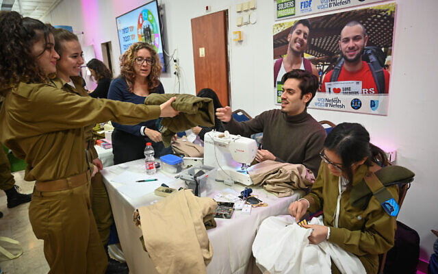 An IDF lone soldier hands a tailor a pair of trousers during an annual 'Errands Day' event in Tel Aviv on February 13, 2020. (Shahar Azran/Nefesh B'Nefesh)