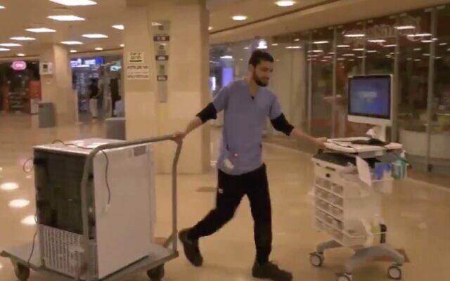An employee of Rambam Medical Center in Haifa moves equipment to a special wing being set up at the hospital to treat the coronavirus, February 29, 2019. (Screen capture: Twitter)