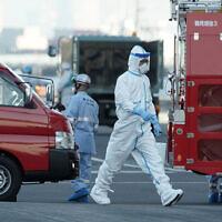 An official walks near the cruise ship Diamond Princess anchored off the Yokohama Port in Yokohama, near Tokyo, February 10, 2020. (AP/Eugene Hoshiko)