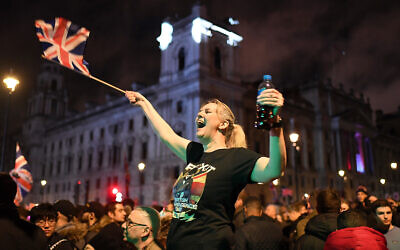 A Brexit supporter celebrates during a rally in Parliament square in London, England, Jan. 31, 2020. (AP Photo/Alberto Pezzali)