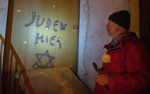 Illustrative: Italian Aldo Rolfi stands in front of the door to his home, where the writing ''Juden Hier,'' German for ''Jews Here,'' with a Star of David, was painted, during a torchlit protest against anti-Semitism, in Mondovi, northern Italy, January 24, 2020. (Marco Alpozzi/LaPresse via AP)