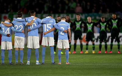 Players from Wolfsburg, rear, and Malmo, front, hold a minute of silence for the victims of the deadly attack in the German city of Hanau prior to a soccer match between VfL Wolfsburg and Malmo FF in Wolfsburg, Germany, Feb. 20, 2020. (AP Photo/Michael Sohn)