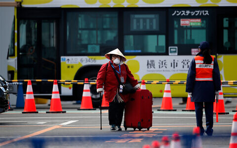 An unidentified passenger walks down after she disembarked from the quarantined Diamond Princess cruise ship, Feb. 19, 2020, in Yokohama, near Tokyo. (AP Photo/Jae C. Hong)