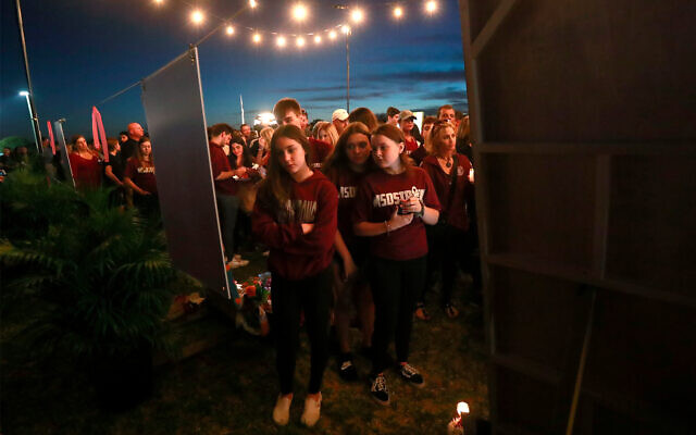 Mourners at an anniversary memorial for the victims of the Parkland, Fla., shooting, Feb. 14, 2019, in Parkland, Fla. (AP Photo/Wilfredo Lee)