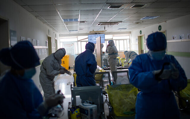 Medical workers put on protective suits before entering an isolation ward in Wuhan in central China's Hubei Province, Feb. 22, 2020. (Cai Yang/Xinhua via AP)