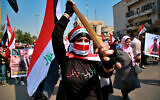 An anti-government protester holds an Iraqi flag during demonstrations in Baghdad, Iraq, Feb. 23, 2020. (AP Photo/Khalid Mohammed)