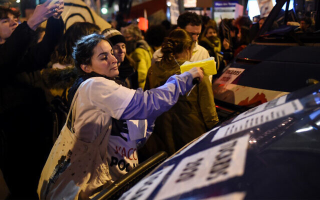 Feminist activists paste posters on police vehicles outside Cesar Film Awards Ceremony in Paris as guests arrive, February 28, 2020. (Lucas Barioulet/AFP)