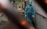 A medical worker wearing a protective suit waits near an entrance of a public housing estate during an evacuation of residents amid a coronavirus outbreak in Hong Kong, Feb. 11, 2020. (AP Photo/Kin Cheung)