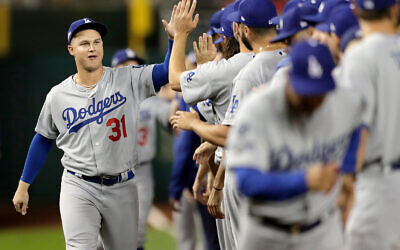 Los Angeles Dodgers right fielder Joc Pederson greets teammates during introductions prior to Game 3 of a baseball National League Division Series against the Washington Nationals, Oct. 6, 2019, in Washington. (AP Photo/Julio Cortez)