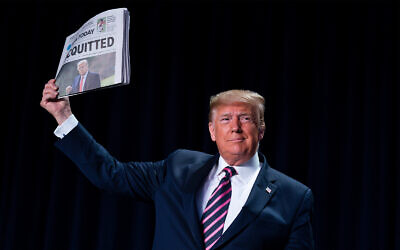 """US President Donald Trump holds up a newspaper with a headline that reads """"ACQUITTED"""" during the 68th annual National Prayer Breakfast, at the Washington Hilton, Feb. 6, 2020, in Washington. (AP Photo/ Evan Vucci)"""