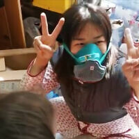 Ofer Dekel's wife, Nana, celebrates finding a protective mask at their apartment in Wuhan, China, in a video posted to Facebook on February 5, 2020. (Facebook screenshot)