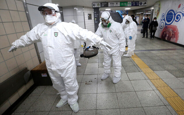 Workers wearing protective gears help clean each other's suits after disinfecting against the coronavirus at a subway station in Seoul, South Korea, Feb. 21, 2020. (AP Photo/Ahn Young-joon)