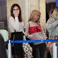 People cover their faces at Ben Gurion International Airport amid coronavirus fears, February 2, 2020. (Avshalom Shoshani/Flash90)