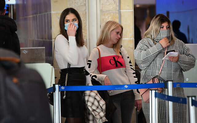 People cover their faces at Ben Gurion International Airport amid coronavirus fears, February 2, 2020. (Avshalom Shoshani/Flash90)