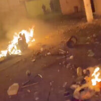 Debris burns at the scene of a brawl in Rahat in footage published by police, February 7, 2020. (Israel police)