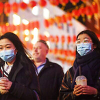 People wearing masks walk in China Town, in London,, Feb. 1, 2020. (Victoria Jones/PA via AP)