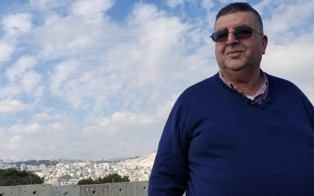 Mayor Ahmad Abu Hilal standing on a building next to the security barrier in Abu Dis on February 3, 2020. (Adam Rasgon/Times of Israel)