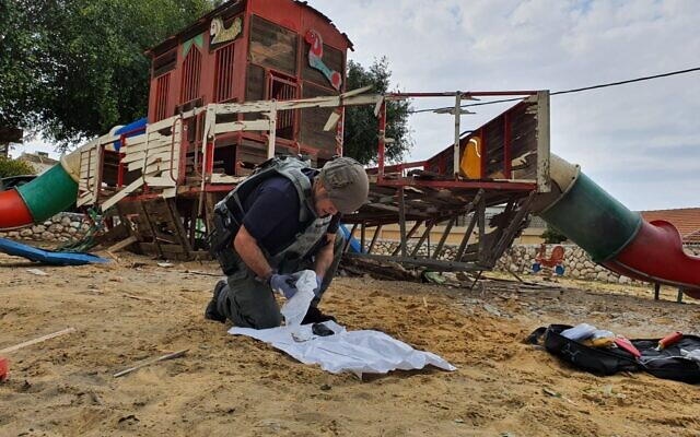 A police sapper removes pieces of a rocket fired from the Gaza Strip that struck a playground in the town of Sderot on February 24, 2020. (Israel Police)