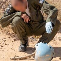 An airman inspects the helmet of an Israeli pilot who died in a plane crash in southern Israel in 1984, in the Paran desert in February 2020. (Israel Defense Forces)