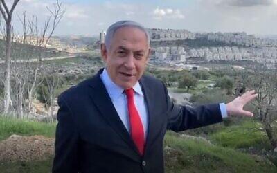 Prime Minister Benjamin Netanyahu speaks in front of the Har Homa neighborhood in East Jerusalem on February 20, 2020. (Screen capture/Twitter)