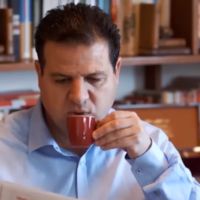 Joint List chief MK Ayman Odeh seen sipping coffee in a Likud campaign ad (video screenshot)