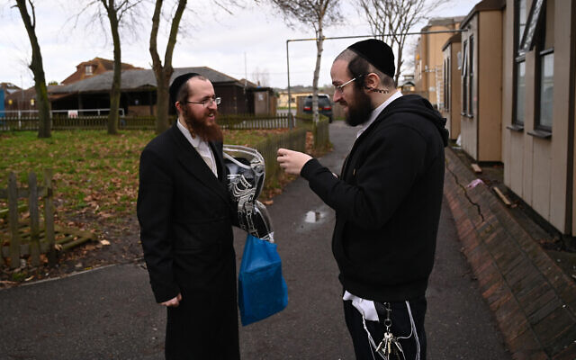 Jacob Gross, right, speaks to a Canvey Island resident outside the town's synagogue, December 13, 2019. (Cnaan Liphshiz/JTA)