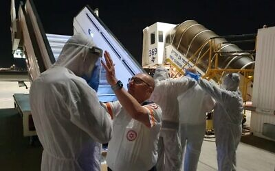 Staff prepare to receive Israelis on a Korean Air plane that landed in Israel, with some 200 other passengers to be refused entry to the country over virus fears (Magen David Adom)