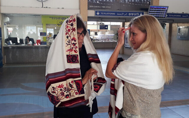 A Women of the Wall member helps a woman lay tefillin at Tel Aviv's Savidor train terminal, February 17, 2020. (Courtesy Women of the Wall)