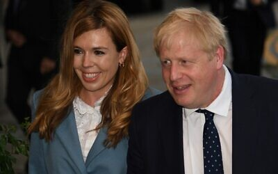 In this file photo taken on September 28, 2019 Britain's Prime Minister Boris Johnson (R) walks with his partner Carrie Symonds as they arrive at The Midland, near the Manchester Central convention complex in Manchester, northwest England, on the eve of the annual Conservative Party conference. (Photo by Oli SCARFF / AFP)