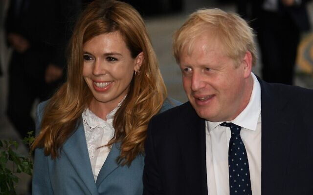 In this photo taken on September 28, 2019, Britain's Prime Minister Boris Johnson (R) walks with his partner Carrie Symonds at The Midland, near the Manchester Central convention complex in Manchester, northwest England, on the eve of the annual Conservative Party conference. (Photo by Oli SCARFF / AFP)