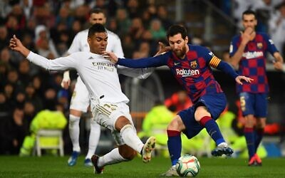 Real Madrid's midfielder Casemiro (L) challenges Barcelona's forward Lionel Messi during the Spanish League soccer match between Real Madrid and Barcelona at the Santiago Bernabeu stadium in Madrid on March 1, 2020. (Gabriel Bouys/AFP)