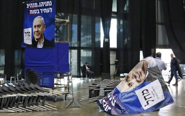 A laborer sorts election posters bearing the portrait of Prime Minister Benjamin Netanyahu, at the Likud party's electoral campaign headquarters in Tel Aviv, on March 2, 2020. (Jack GUEZ / AFP)