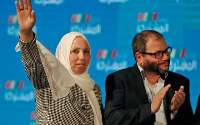 Iman Khatib Yassin, Israeli-Arab politician representing the southern branch of the Islamic Movement in the Joint List electoral alliance, holds up her hand as she stands next to Ofer Cassif, Jewish member and candidate for the Hadash party within the alliance, as they stand before supporters at their electoral headquarters in Israel's northern city of Shfaram on March 2, 2020, after polls officially closed. (Photo by Ahmad GHARABLI / AFP)