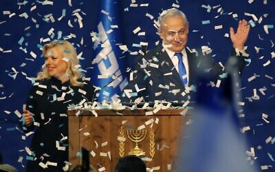 Prime Minister Benjamin Netanyahu and his wife Sara address supporters as confetti falls upon them at the Likud party campaign headquarters in Tel Aviv early on March 3, 2020 (GIL COHEN-MAGEN / AFP)