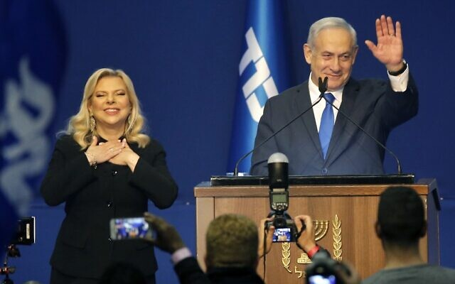 Prime Minister Benjamin Netanyahu (right) and his wife Sara address supporters at the Likud party campaign headquarters in the coastal city of Tel Aviv early on March 3, 2020, after polls officially closed. (GIL COHEN-MAGEN / AFP)