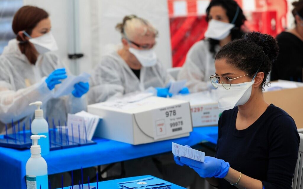 Electoral workers count ballots cast by Israelis under home quarantine after returning from coronavirus infected zones,  in the central town of Shoham on March 4, 2020. (Emmanuel Dunand/AFP)