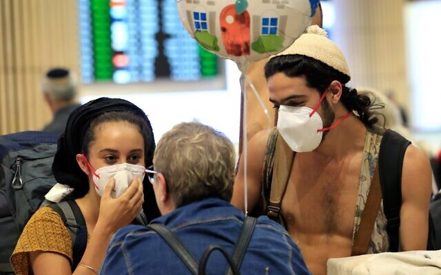 A young couple wearing protective masks are greeted upon arrival at Ben Gurion airport in Israel on March 4, 2020. (Emmanuel DUNAND / AFP)