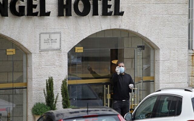 A Palestinian man wearing a protective mask stands at the entrance to a hotel in the West Bank city of Bethlehem on March 6, 2020, following a lockdown on the biblical city after the first Palestinian cases of the deadly coronavirus were discovered there. (Musa Al Shaer/AFP)