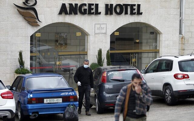 Palestinian men, one of them wearing a protective mask, walk out of the Angel Hotel hotel in the West Bank city of Bethlehem on March 6, 2020. (Musa Al Shaer/AFP)