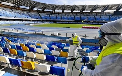 Cleaners wearing protective suits as they sanitize the seats of the San Paolo stadium in Naples, Italy, March 4, 2020. (CIRO FUSCO/ANSA/AFP)