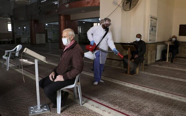 An elderly man wearing a protective masks reads from the Quran while seated in a mosque being sterilized by Palestinian Authority health workers in the West Bank city of Ramallah to prevent the spread of the coronavirus, March 7, 2020. (Abbas Momani/AFP)