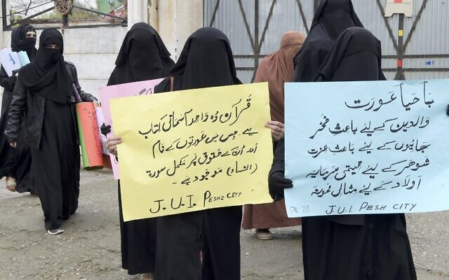Burqa-clad female activists of Islamic political party Jamiat Ulema-e-Islam (JUI-F), carry placards during a rally to mark the International Women's Day in Peshawar on March 8, 2020 (Abdul MAJEED / AFP)