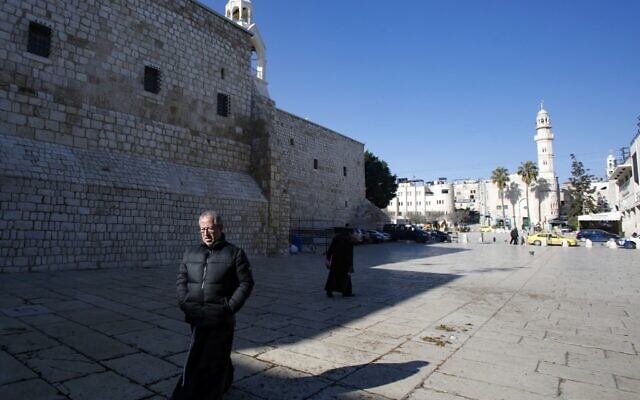 A priest walks in the Church of the Nativity compound in the West Bank city of Bethlehem on March 8, 2020, after it came under lockdown two days ago as an emergency measure to limit the spread of the novel coronavirus. (Musa Al SHAER / AFP)