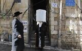 An ultra-Orthodox Jewish boy dressed in a costume as an elderly ultra-Orthodox Jew walks by an elderly ultra-Orthodox Jew (who is not in costume), two days ahead of the official holiday of Purim, in the Mea Shearim neighborhood in Jerusalem, on March 8, 2020. (MENAHEM KAHANA / AFP)