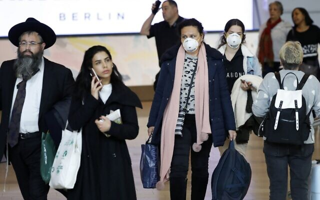 Passengers wearing protective masks in the arrivals halls at Ben Gurion International Airport near Tel Aviv on March 10, 2020. (Jack Guez/AFP)