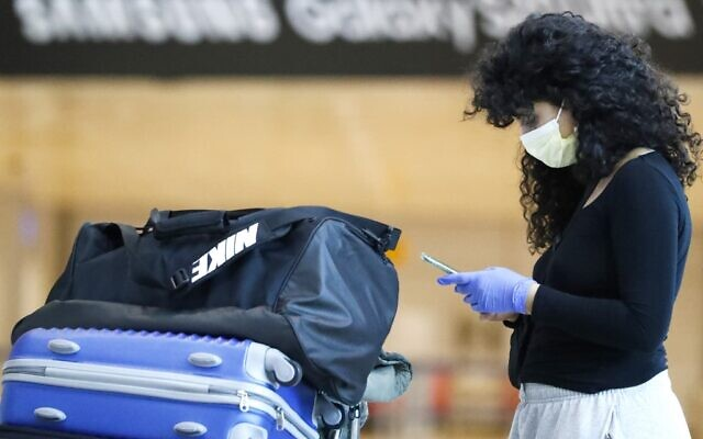 A traveler wearing a protective mask checks her phone at the arrivals hall of Ben Gurion International Airport near Tel Aviv on March 10, 2020. (Jack Guez/AFP)