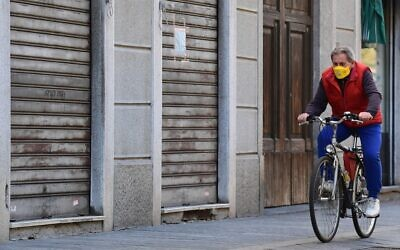 A man wearing a protective mask rides a bicycle past closed shops in a deserted street of central Codogno, southeast of Milan, on March 11, 2020, a day after Italy imposed unprecedented national restrictions to control the deadly COVID-19 coronavirus. (Miguel Medina/AFP)