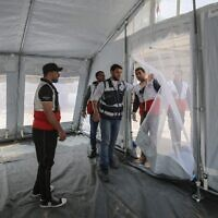 Members of the Palestinian Ministry of Health in partnership with the World Health Organisation (WHO), set up outdoor tents for the preliminary medical examination of suspected coronavirus patients at the Rafah border crossing with Egypt in the southern Gaza Strip on March 12, 2020. (Photo by SAID KHATIB / AFP)