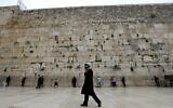 An ultra-Orthodox Jewish man walks past people praying at the nearly deserted Western Wall in Jerusalem's Old City on March 12, 2020. (Emmanuel Dunand/AFP)