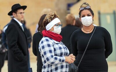 Women wearing protective masks visit the nearly deserted Western Wall in Jerusalem's Old City on March 12, 2020, after Israel imposed some of the world's tightest restrictions to contain the new coronavirus. (Emmanuel Dunand/AFP)